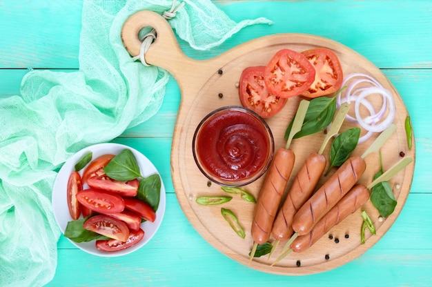 Salsichas suculentas no espeto com tomate e molho de tomate na tábua redonda