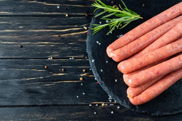 Salsichas suculentas para churrasco mentem sobre uma tábua de pedra com alecrim e especiarias