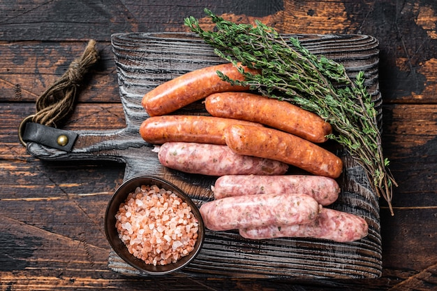 Salsichas variadas de porco cru e bovino com especiarias em uma placa de madeira com tomilho. fundo de madeira escuro. vista do topo.