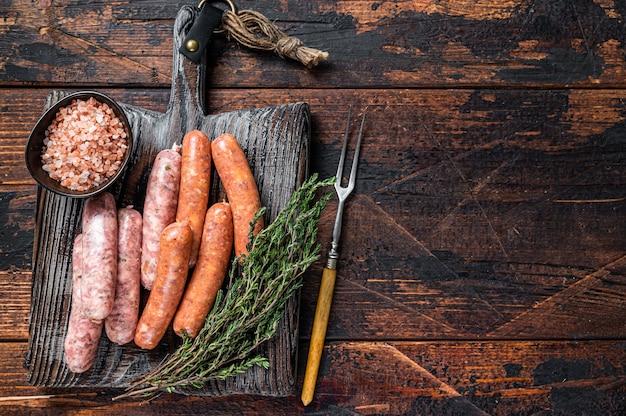 Salsichas variadas de porco cru e bovino com especiarias em uma placa de madeira com tomilho