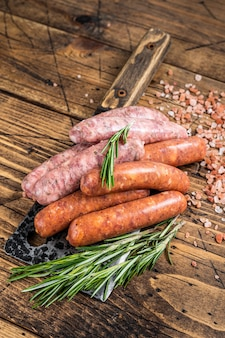 Salsichas variadas de porco cru e bovino em um cutelo de açougueiro