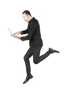 Saltar o empresário com o computador portátil isolado no branco