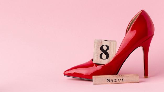 Salto alto vermelho com letras de 8 de março