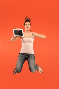 Salto de jovem sobre fundo azul do estúdio usando laptop ou tablet gadget enquanto pula. garota correndo em movimento ou movimento.