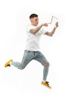 Salto de jovem sobre fundo branco do estúdio usando o computador portátil enquanto salta.