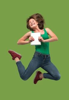 Salto de jovem sobre fundo verde studio usando laptop ou tablet gadget enquanto pula.