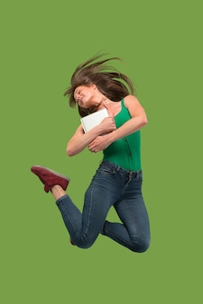 Salto de mulher jovem sobre o verde usando laptop ou tablet gadget enquanto pula. garota correndo em movimento ou movimento