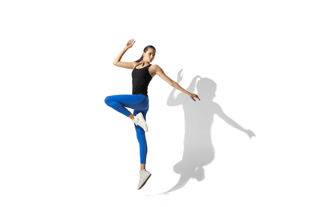 Salto em altura bela jovem atleta feminina, treinamento de alongamento no fundo branco do estúdio