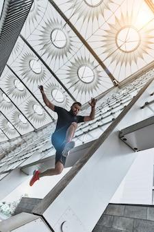 Salto em comprimento no ar. jovem bonito em roupas esportivas pulando