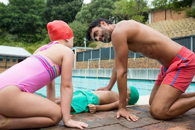 Salva-vidas ajudando menino inconsciente enquanto interage com a menina perto da piscina