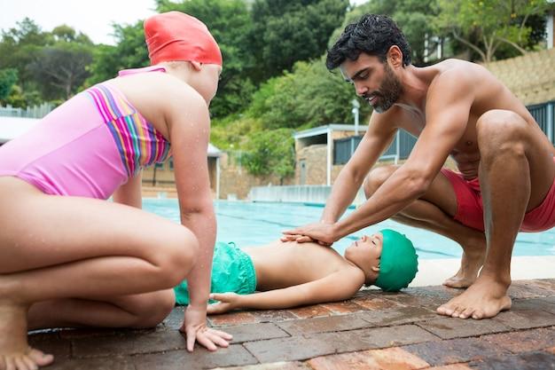 Salva-vidas ajudando menino inconsciente perto da piscina