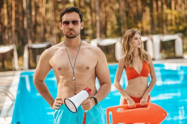 Salva-vidas. dois salva-vidas de piscina em pé perto da piscina pública