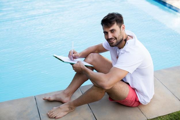 Salva-vidas escrevendo na prancheta ao lado da piscina em um dia ensolarado
