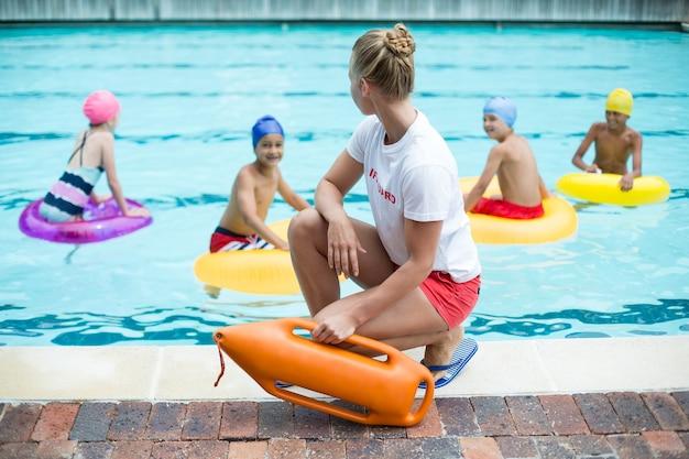 Salva-vidas feminino segurando a lata de resgate enquanto crianças nadam na piscina