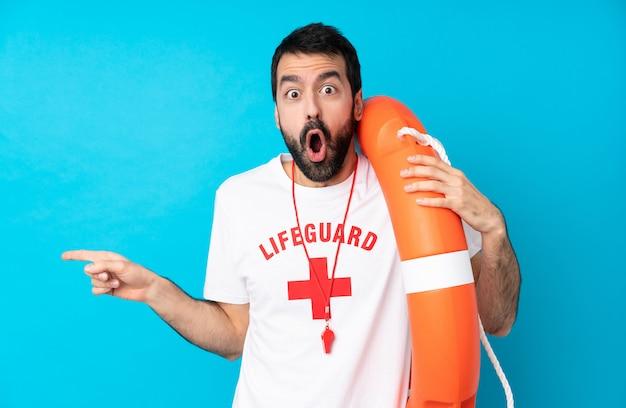 Salva-vidas homem azul surpreso e apontando o dedo para o lado