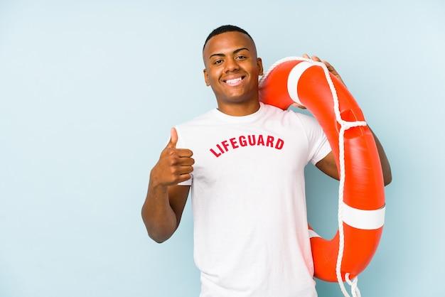 Salva-vidas latino jovem isolado no azul, sorrindo e levantando o polegar