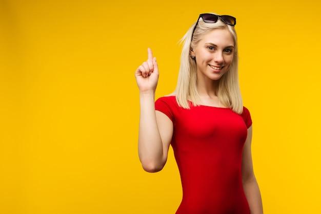 Salva-vidas loira bonita em maiô vermelho e óculos de sol aponta o dedo para cima