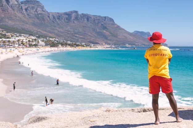 Salva-vidas na cidade do cabo assistindo a famosa praia de camps bay com água turquesa