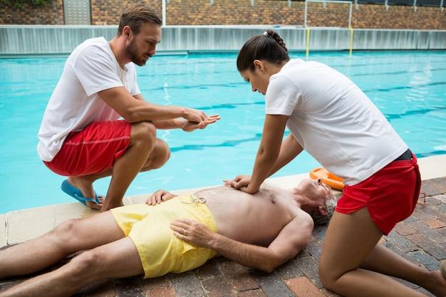 Salva-vidas pressionando o peito de um homem idoso inconsciente à beira da piscina