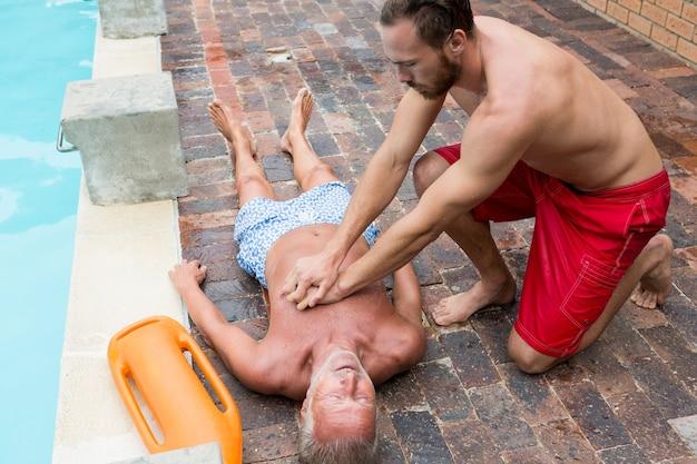Salva-vidas pressionando o peito de um homem sênior inconsciente à beira da piscina