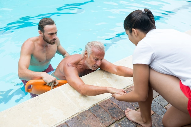 Salva-vidas resgatando homem idoso inconsciente da piscina