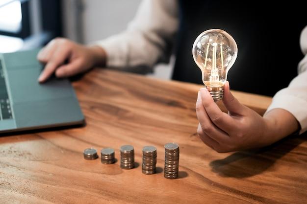 Salvando a ideia de moedas com lâmpada para inovação e ideia de conceito de investimento.