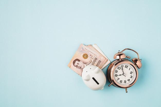 Salvando cofrinho com moeda tailandesa, 1000 baht, notas de dinheiro da tailândia e despertador com sino em fundo azul para negócios, finanças e conceito de gerenciamento de tempo
