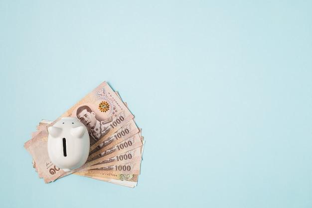 Salvando cofrinho com moeda tailandesa, 1000 baht, notas de dinheiro da tailândia em fundo azul para negócios e conceito de finanças