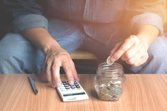 Salvando o conceito de dinheiro e mão colocando moedas de dinheiro no frasco de vidro para financeira