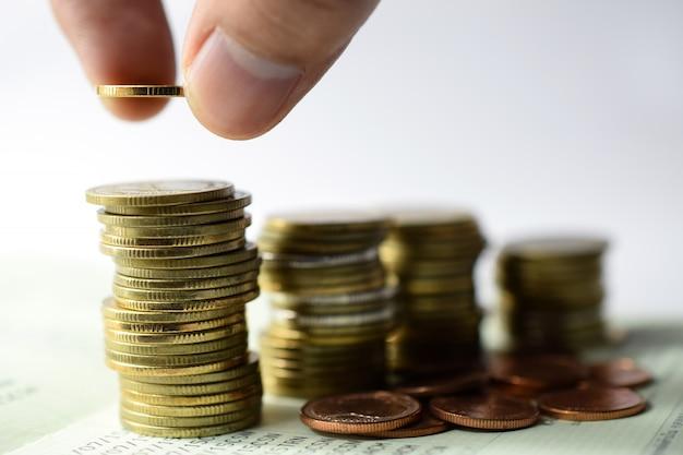 Salvando o conceito de dinheiro predefinido por mão colocando dinheiro moeda pilha crescente negócio
