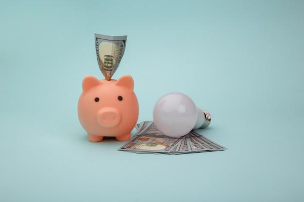 Salvando o conceito de eletricidade. lâmpada led e cofrinho com notas de dinheiro