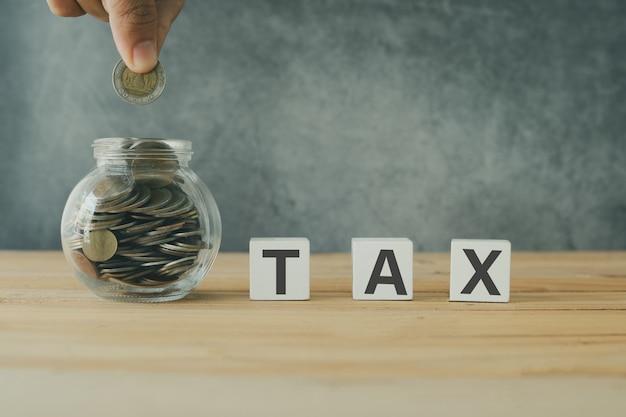 Salvando o conceito de imposto, imposto este último em madeira com a mão colocar moeda no pote, cheio de dinheiro na mesa de madeira
