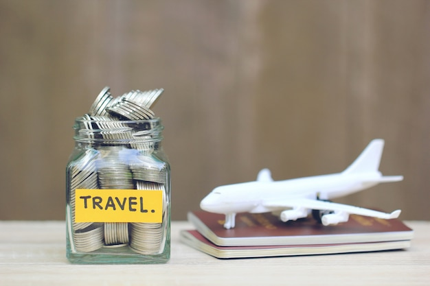 Salvando o planejamento para o orçamento de viagens do conceito de férias, financeiro, pilha de moedas dinheiro no frasco de vidro e o avião no passaporte
