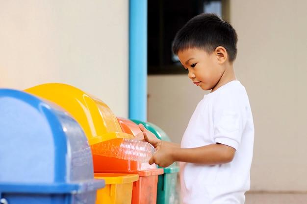 Salvar o conceito ambiental, um menino da criança que joga uma garrafa plástica em uma reciclagem.