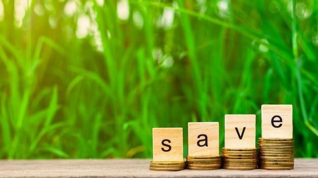 Salve a pilha de palavra de moedas e uma pilha de moedas de ouro na mesa de madeira