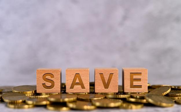 Salve as letras do cubo de madeira do alfabeto palavra colocadas em uma moeda de ouro