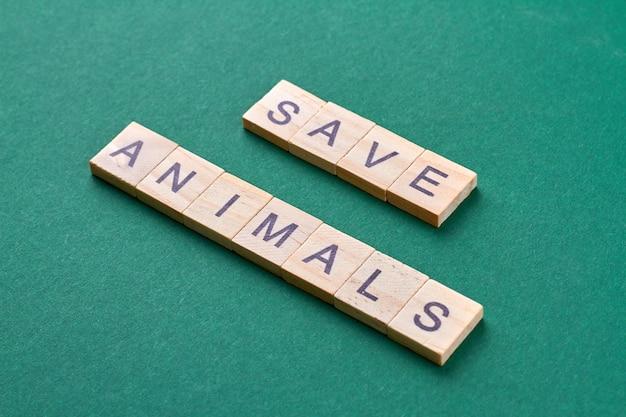 Salve o conceito de animais. palavras feitas de blocos de madeira isoladas sobre fundo verde.
