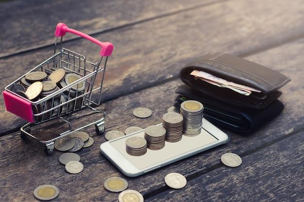 Salve o conceito de dinheiro com a pilha de moedas crescendo no smartphone, carrinho e carteira