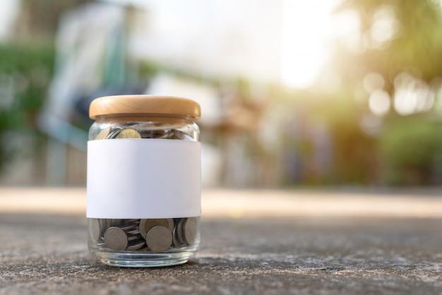 Salve o conceito de dinheiro com moedas na garrafa com espaço de cópia