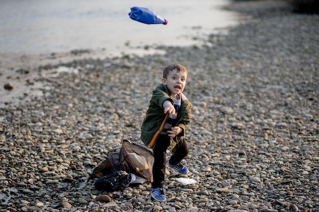 Salve o conceito de meio ambiente, um garotinho recolhendo lixo e garrafas plásticas na praia para despejar no lixo.