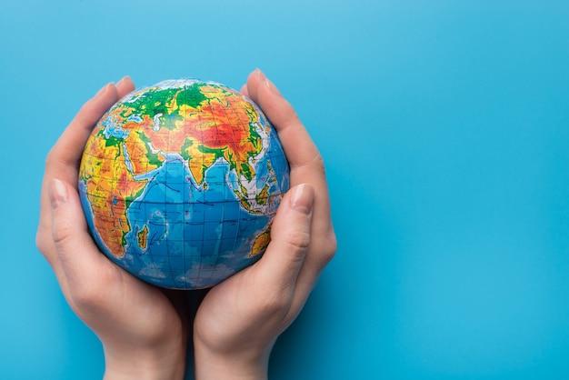 Salve o conceito de planeta. feche a foto de uma mulher segurando o planeta em um fundo azul com um espaço vazio de cópia em branco para o texto
