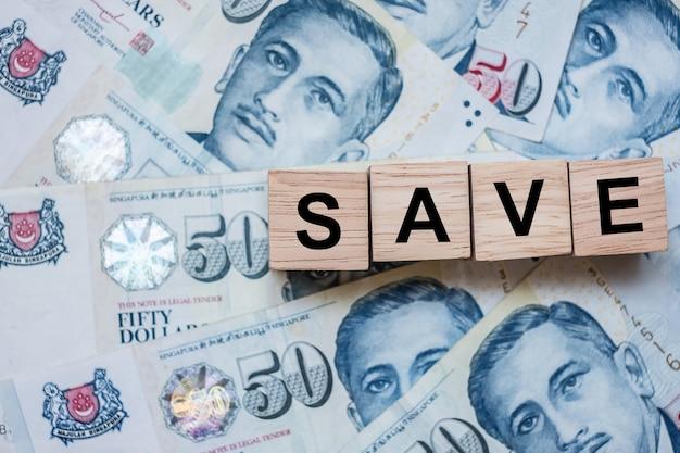 Salve o cubo de madeira em cinquenta dólares de cingapura fundo da cédula.