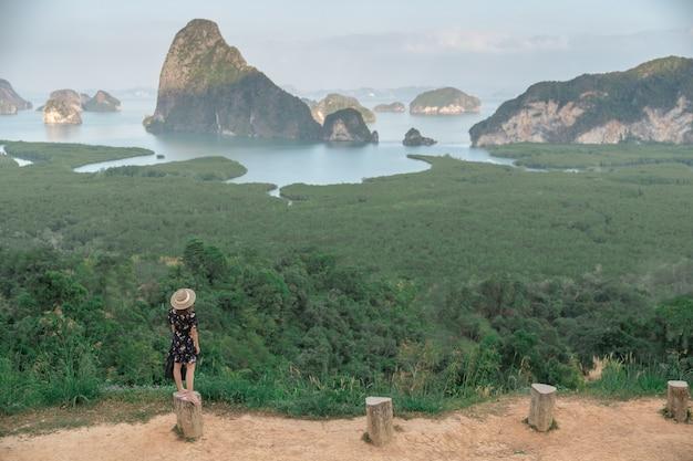 Samed nang chee. mulher com vista para a baía de phang nga, floresta de manguezais e colinas no mar de andaman, tailândia.