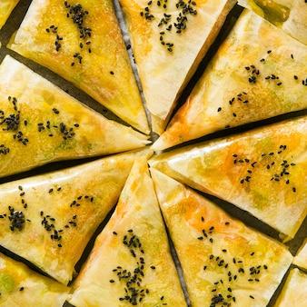Samosa indiana feita de massa folhada com batata picante e legumes em uma assadeira, pronta para ser assada no forno com sementes de gergelim preto