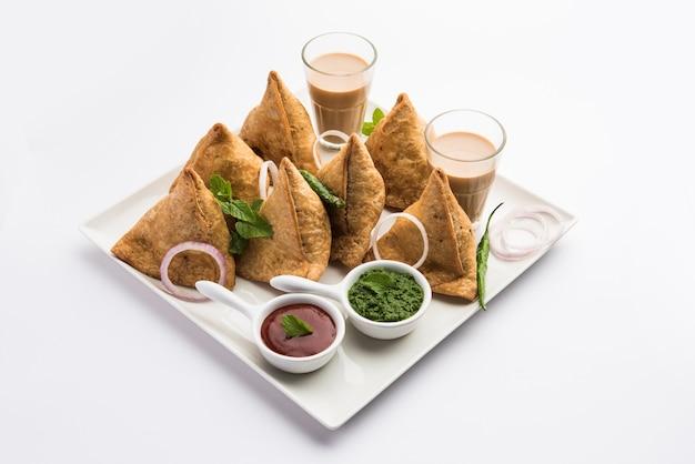 Samosa - pastelaria frita / assada em forma de triângulo com recheio saboroso, populares snacks indian tea time, servido com chutney verde e ketchup de tomate