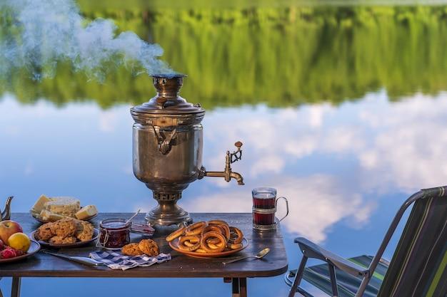 Samovar de chá de metal vintage com fumaça branca e comida na mesa perto do lago de água calma na floresta verde na manhã, ucrânia. conceito de comida natural