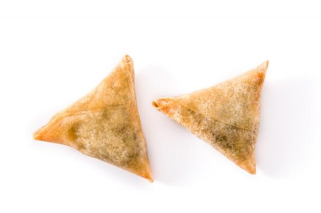 Samsa ou samosas com carne e legumes isolados no branco.