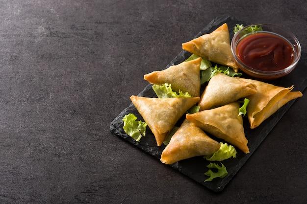 Samsa ou samosas com carne e legumes no preto. comida indiana tradicional.