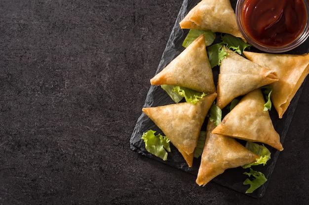 Samsa ou samosas com carne e legumes no preto. copyspace