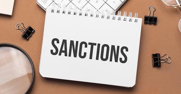 Sanções no bloco de notas com caneta, óculos e calculadora